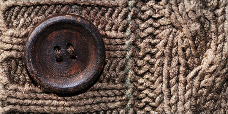 Button on a brown knitted cardigan